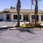 Front of the community hall with center water fountain and palm trees, surrounded by ample parking space for guests.