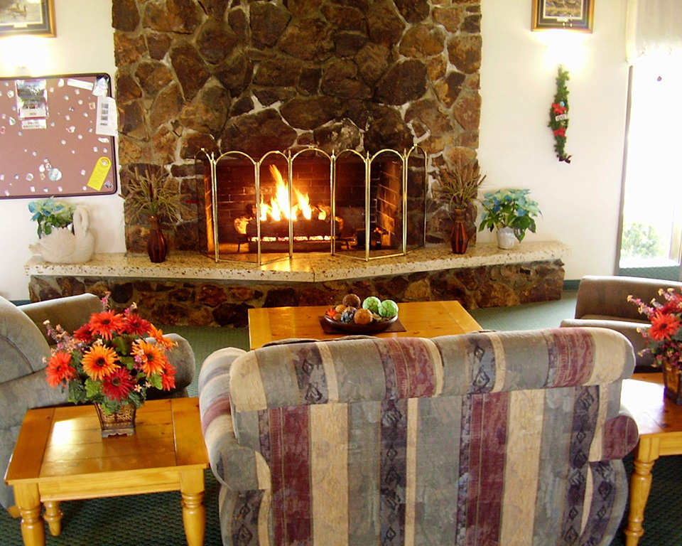 Tranquil community center with stone fireplace surrounded by couches for peaceful relaxation
