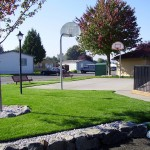 Outdoor basketball court adjacent to the playground. Surrounded by green grass and a walkway that cuts through. Two benches sit on the outer end.