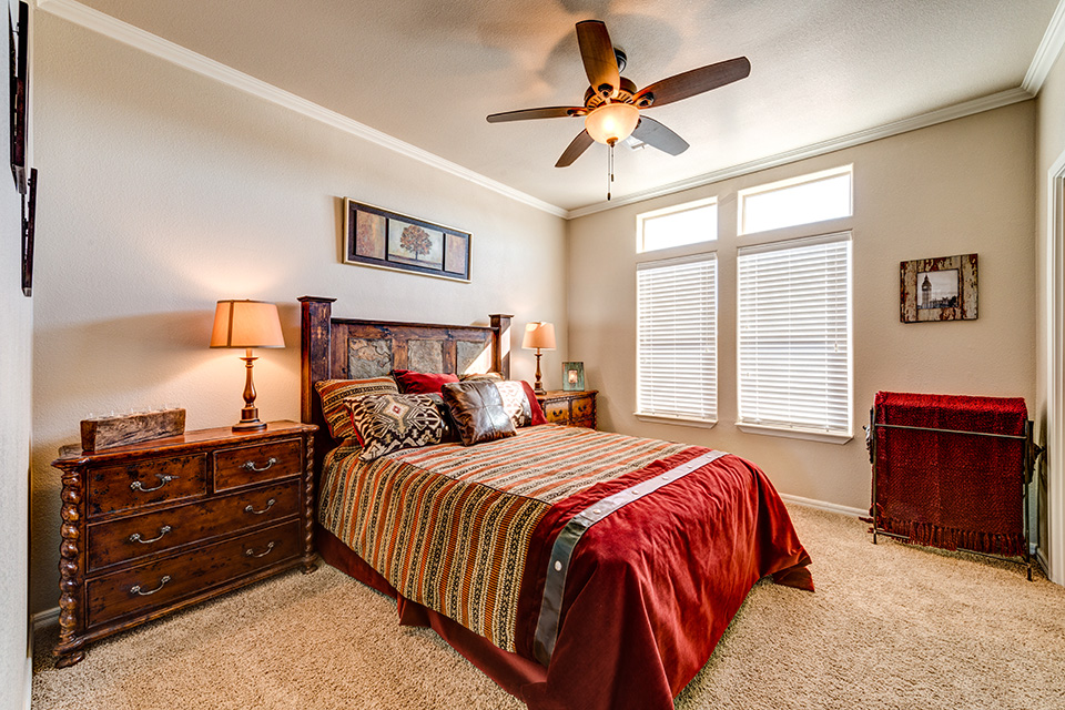 Red, tan, and brown theme bedroom. Dark wood bed frame and night stands with lamps. Ceiling fan combined with light and large window on the wall for natural light.