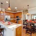 Updated L shaped kitchen with wood cabinets, stainless steel appliances, and white counter tops. Hanging ceiling lights over seating areas. Ample eating space on either the elevated counter or on the circular kitchen table, all equipped with tall dark colored bar chairs.