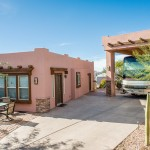 Light pink manufactured home with brown window trimmings and short stone corners. Small front patio area with table and chairs. Adjacent carport similar in style to the home, large enough to fit an RV. Clean, paved, and well maintained property.