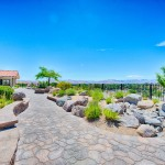 A cobblestone walkway takes you around the community center with desert landscaping on both side. Small shrubs and rocks. Views of the mountains.