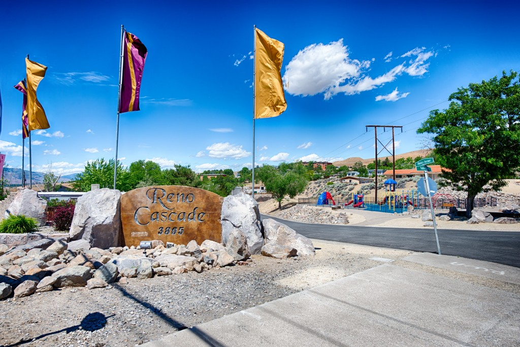 Reno Cascade entrance has a sign etched in stone. Gold and purple flags fly above and around sign.