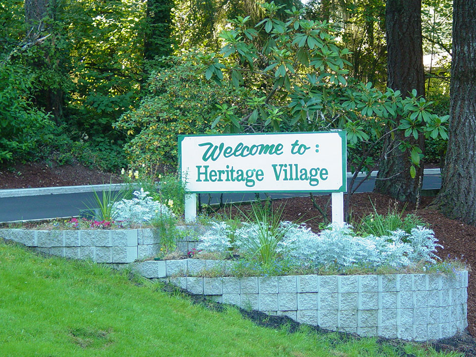 Welcome to Heritage Village wood sign cream with green wording. Lush green landscape all around. Small flowers planted around sign.