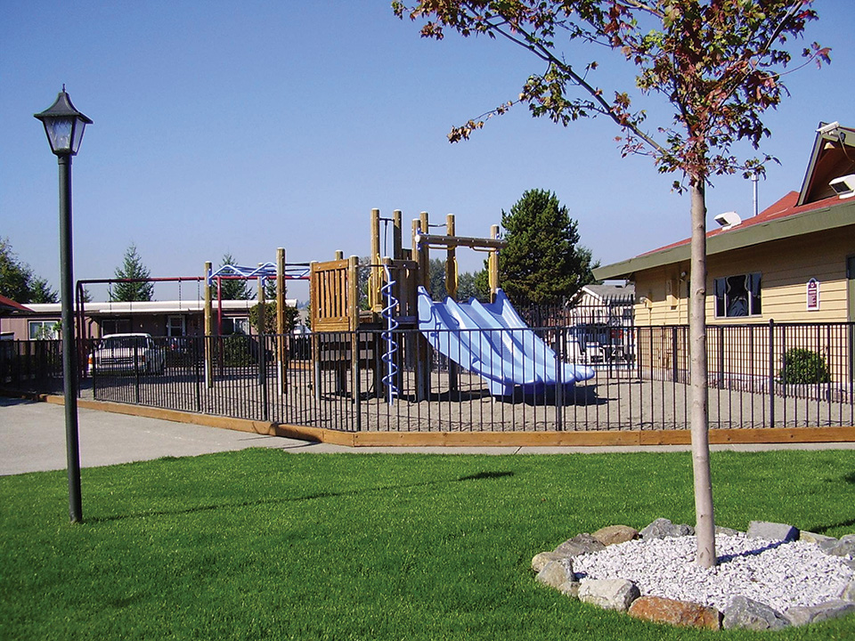 Outdoor playground enclosed by gate. Sand covers the ground throughout and a grass area outside of the gates.