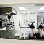 Very modern commercial kitchen is located in the clubhouse. Stainless steel oven, fridge, and ice chest. Large island with sink. White cabinets with dark granitetops for counters.