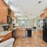 Beautiful modern and open kitchen. Wood cabinets and new black appliances. Tile floor throughout and recessed lighting.