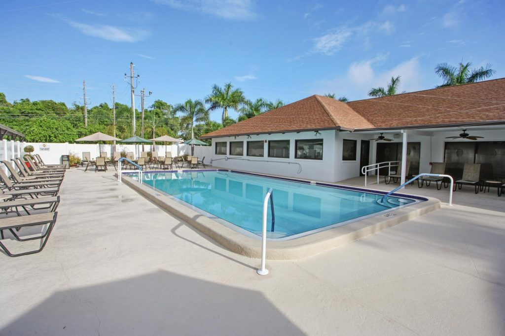 Calm swimming pool with lounge chairs and patio furniture with chairs, tables, and umbrellas. located outside clubhouse.