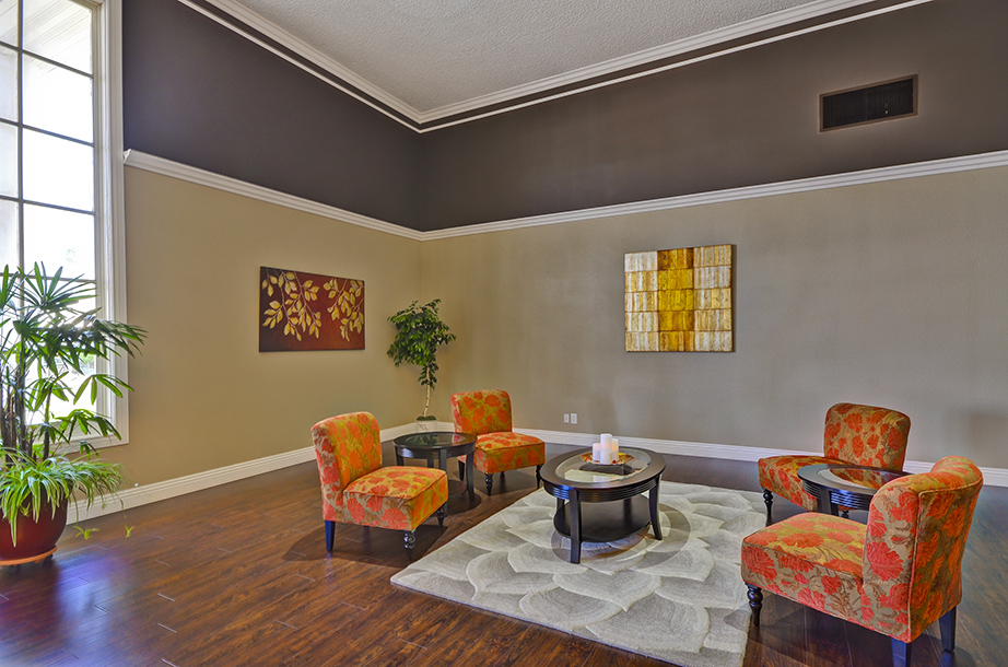 Modern and open concept clubhouse. The warm tones of orange, brown, and yellow create a welcoming home feel. Circular seat arrangement allow residents to lounge and relax.