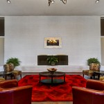 Beautifully decorated, modern clubhouse. Comfortable lounge chairs surround a vibrant bright red rug in the center. Dark wood flooring and tan walls with chocolate trimmings create a warm feel.