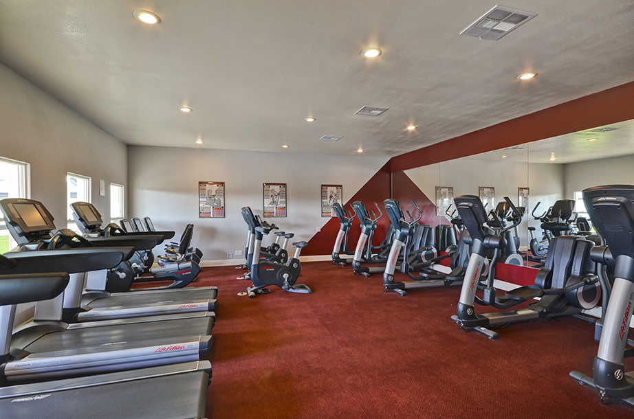 The fitness center, one of the many amenities of the community, includes a multitude of equipment. Treadmills, ellipticals, and stationary bikes sit on dark red carpet and provides a space for residents to freely exercise.