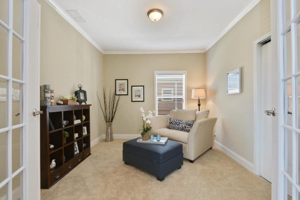 An extra room in the new home can be suited as a den or office. White french doors open into the room with tan carpet. Crown molding around the top and bottom and light beige color the walls. An oversized tan chair and blue ottoman decorate the room. A wide dark wood bookcase, and silver vase with fake shrubbery decorate the room.