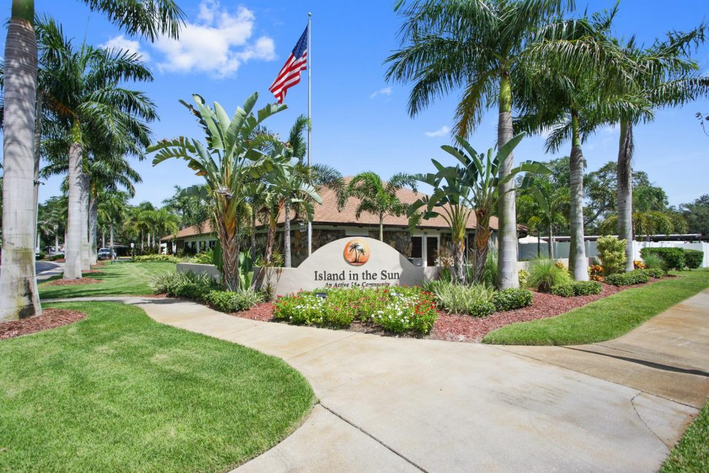 Island in the Sun, an active 55+ community has a well landscaped entrance with palm trees and green grass. An American flag flies high above the Island in the Sun sign.
