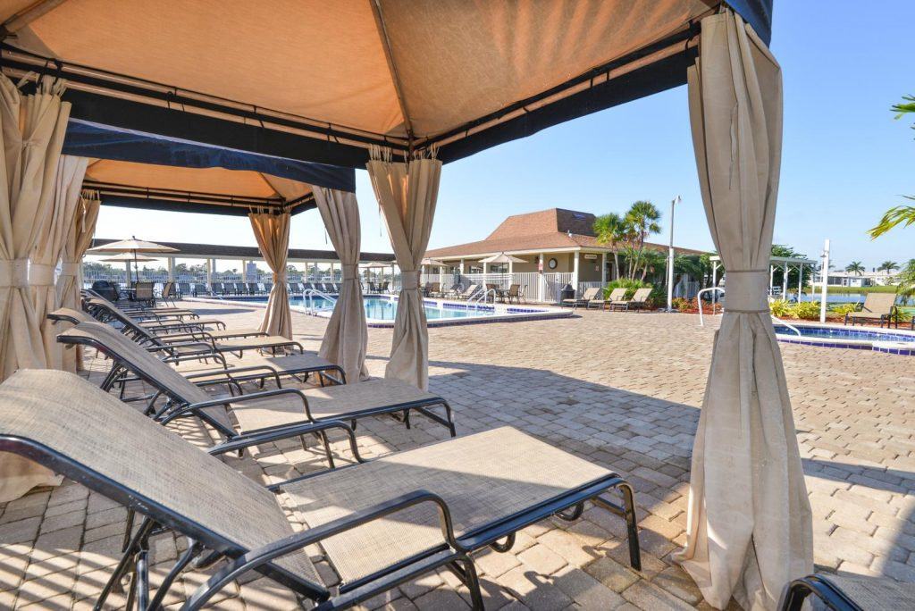 Large cabanas with lounge chairs offer shad in pool area.
