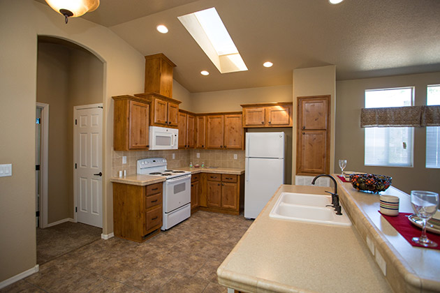 A new, spacious, open kitchen. Features vaulted ceilings and recessed lighting and a skylight. An island in the middle with a white sink. White microwave, fridge and oven.