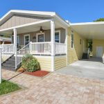 New manufactured home painted grey with light yellow siding. Covered carport with small shed at end of carport. Covered front porch with two ceiling fans. Pavers make up small driveway and walkway up to porch steps. White lamppost at end of front yard.