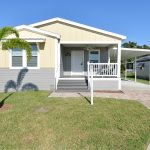 Beautiful new home with two tone colors of cream and light gray. Small covered front porch with ceiling fan. Four small steps take you from the porch to the walk way and driveway. Attached carport. Small palm tree growing in the front yard.