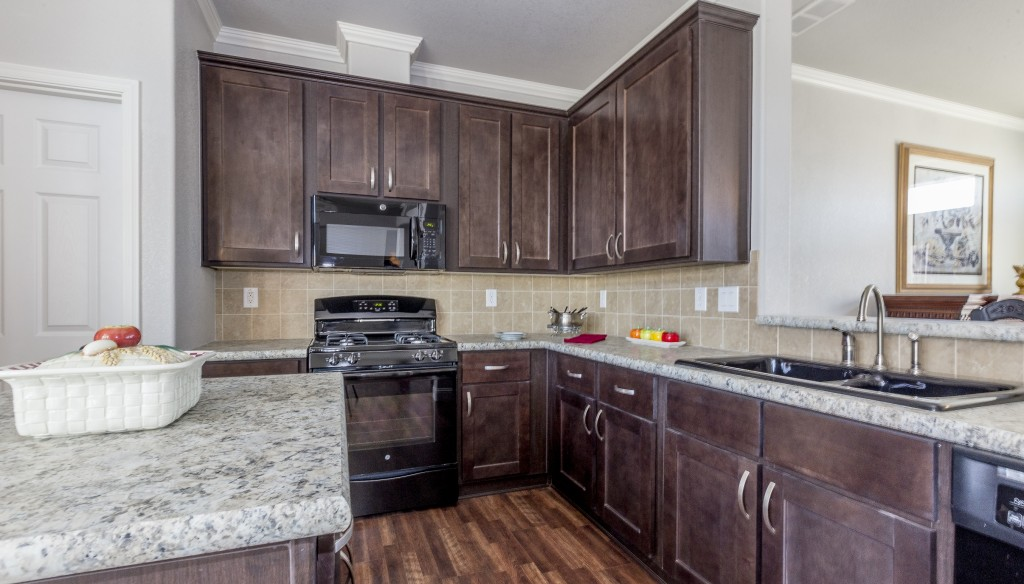 A brand new kitchen with hardwood floor and dark wood cabinets. Black appliances. Granite countertops. Kitchen island.