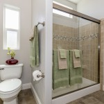Hardwood floors in bathroom. Sage green and tan towels. Toilet and step in shower with decorative tiles.