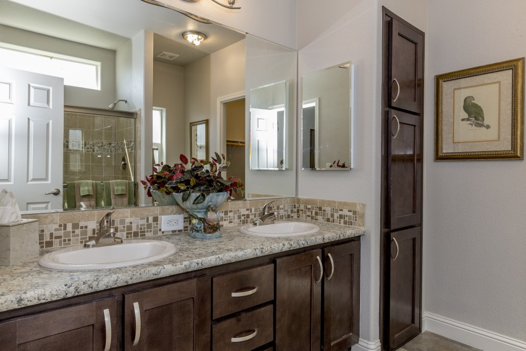 A new bathroom with dual sinks. Dark wood cabinets with granite countertops. Tile flooring.