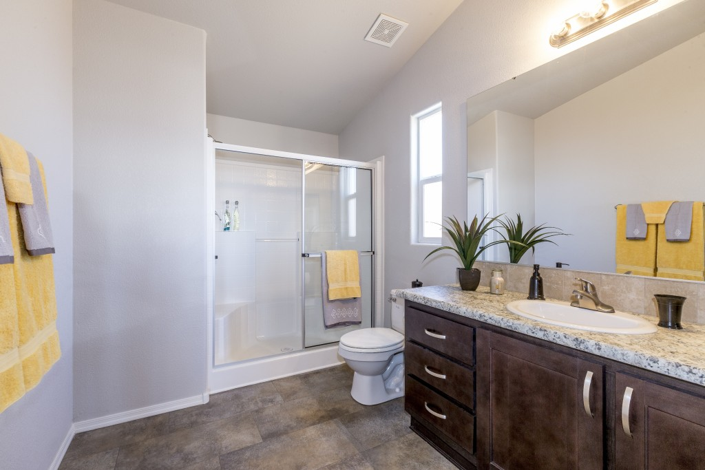 Bright new bathroom with yellow and gray towels. Vaulted ceilings and tile flooring. Wood cabinets. Step in shower with little seating area. Glass shower door.