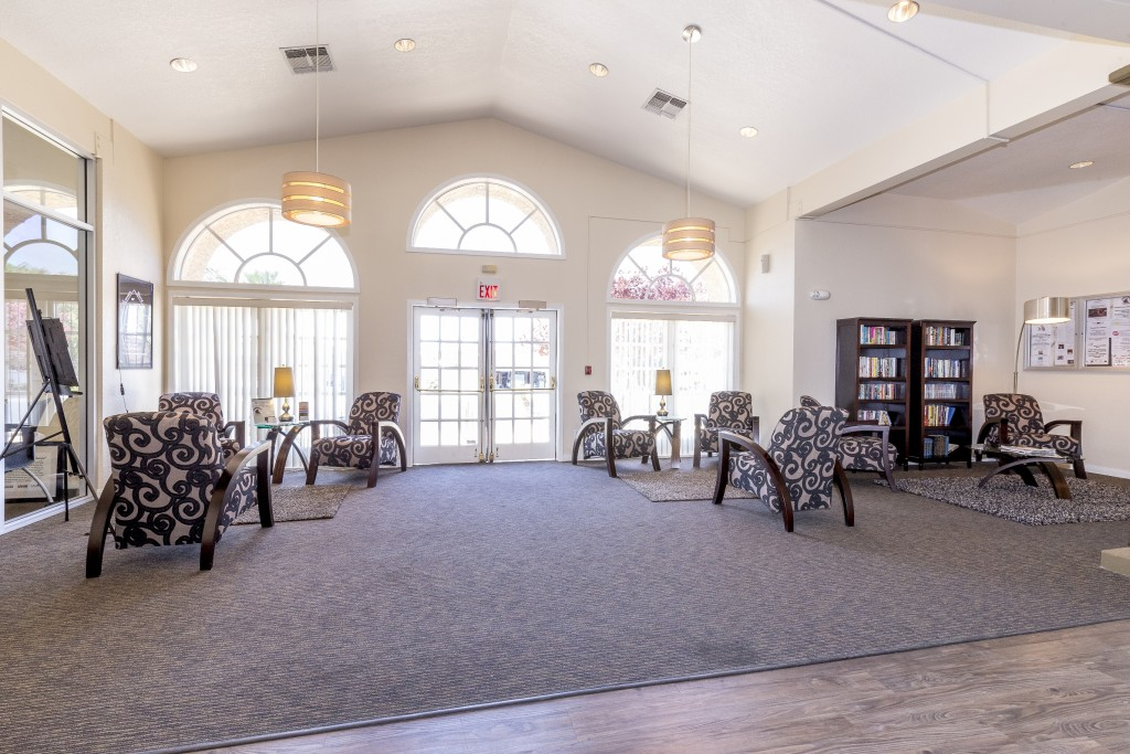 Clubhouse with mini library. Comfy chairs with tables and lamps for reading. Lots of natural light with tall windows with arches.
