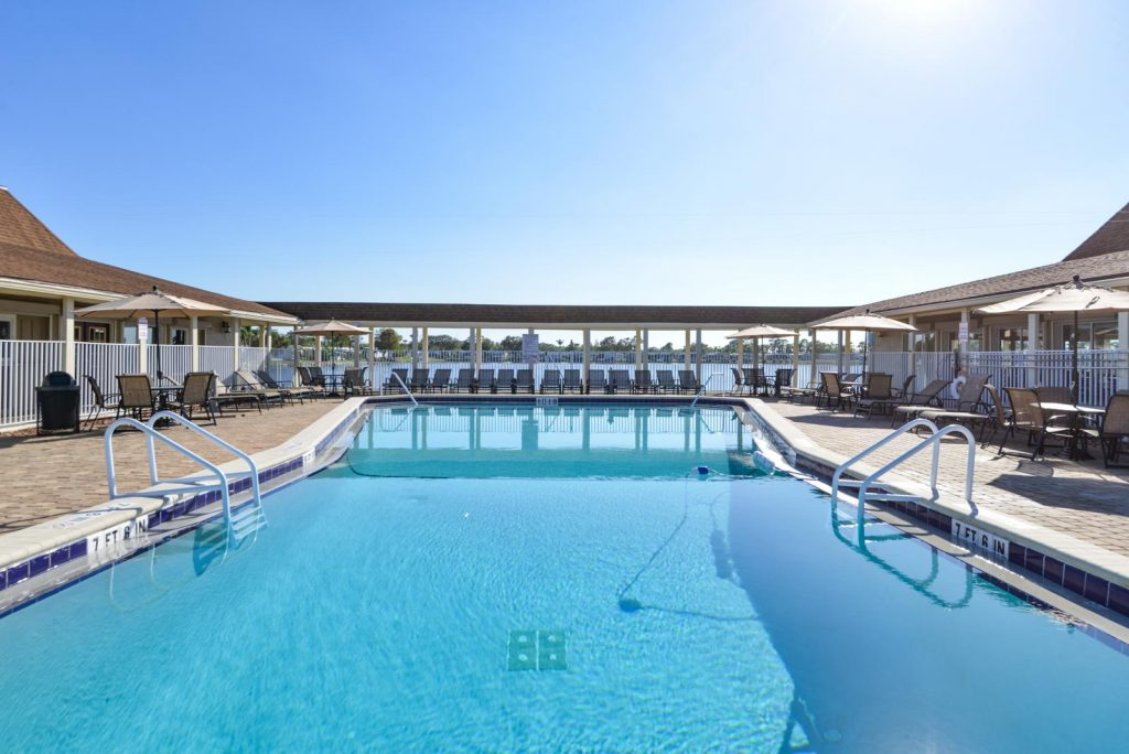 Resort style pool with calm waters and pool furniture all around with lounge chairs and tables with umbrellas.