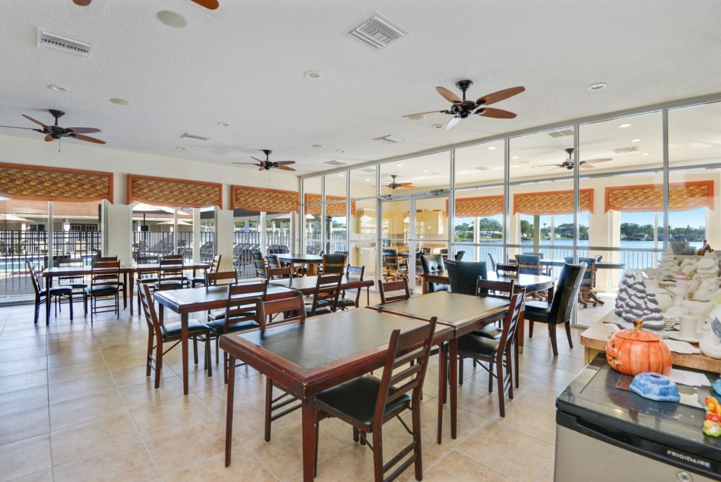 Clubhouse with tables and chairs to sit in and overlook the lake.