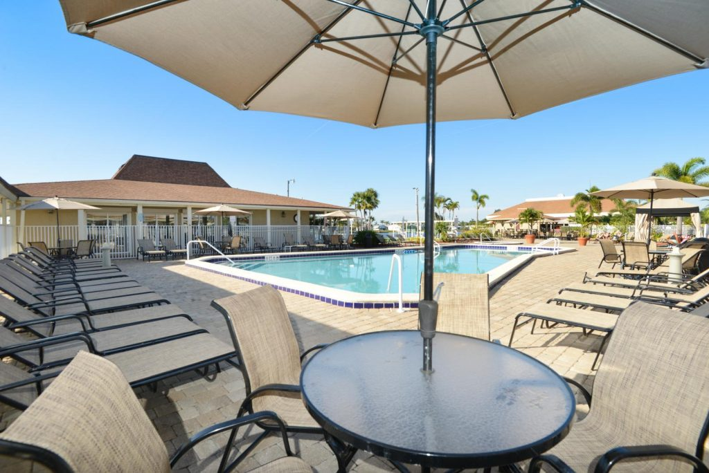 Pool furniture with lounge chairs and tables with umbrellas surround the pool.