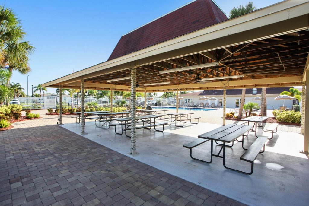 Large covered cabana with picnic tables and seating.