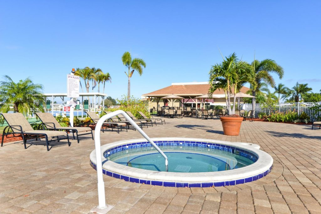 Jacuzzi is set among lounge chairs and palm trees.