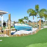 Mini golf course with clean greens. A blue fishing boat sits upon white rocks with palm trees along the course.
