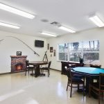 Bright game room with card tables. Giant fish and fishing rod on wall for decor.