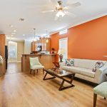 Modern styled living room with painted orange walls acccented with white crown molding. Light wood flooring runs throughout. Two dark end tables are on each side of off white couch. Dark wood coffee table in front of couch.