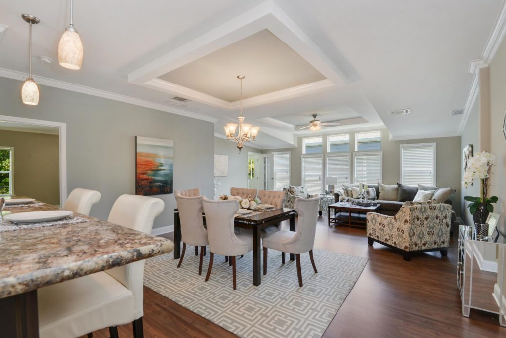 Beautiful modern living room with hardwood floors throughout. Tall ceilings with crown molding running throughout the top and bottom of walls. A light grey color is on the walls with floor to ceiling windows. Granite breakfast nook with 2 chairs. A dark wood dining table seats six and sits atop a patterned grey and white rug.