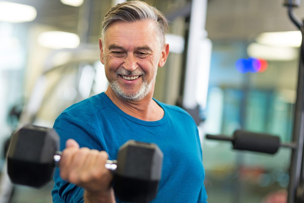 A 55+ man works out in fitness center and curls arm with free weight.