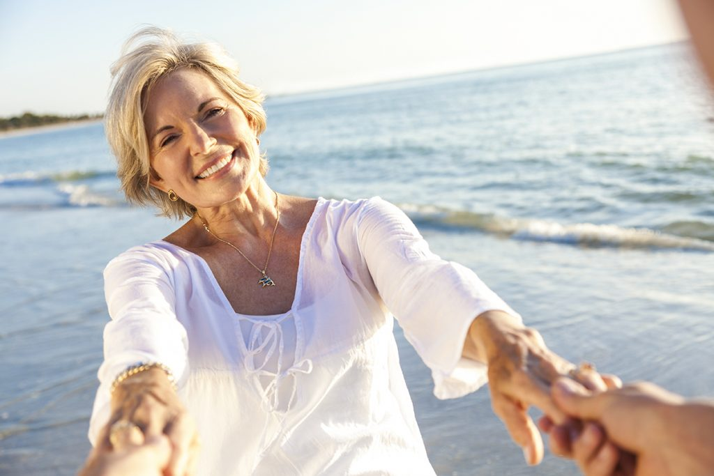 Happy senior man and woman couple walking or dancing and holding hands on a beach