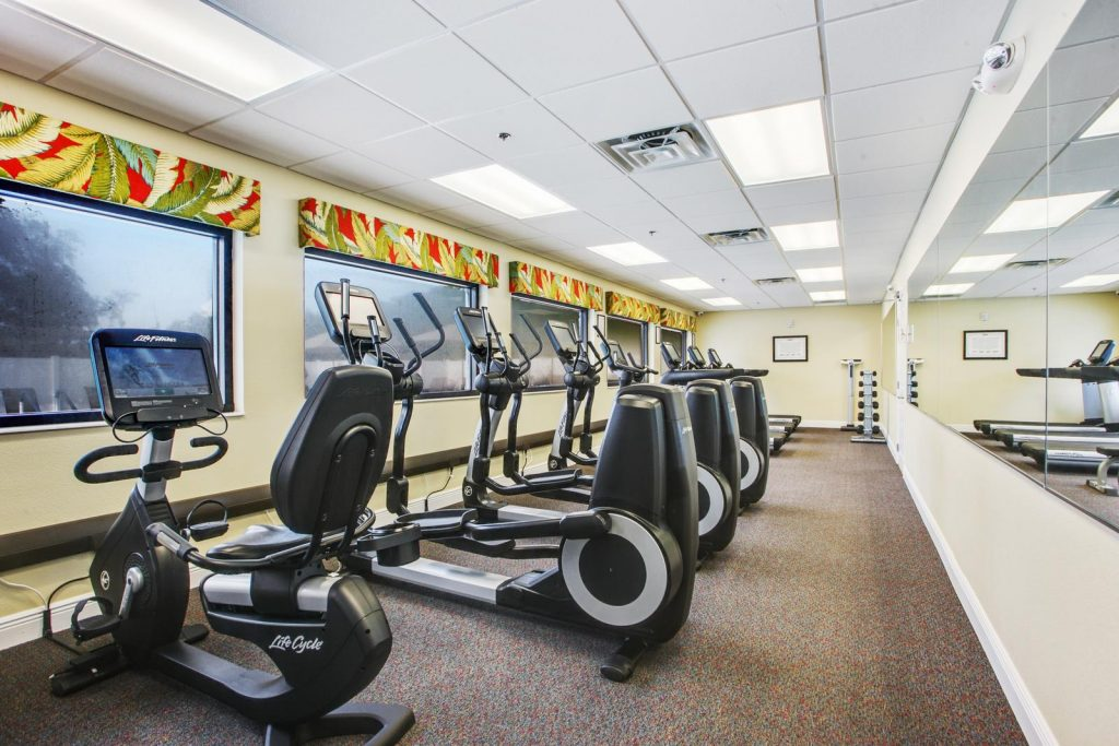 Long exercise room with stationary bikes, elliptical machines, treadmills and free weights.