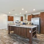 Beautiful modern kitchen with stainless steel refrigerator, range hood and oven and wood flooring throughout. Large kitchen island in the middle with granite counter tops and dark wood base. Shelves for storage and sink built into island.