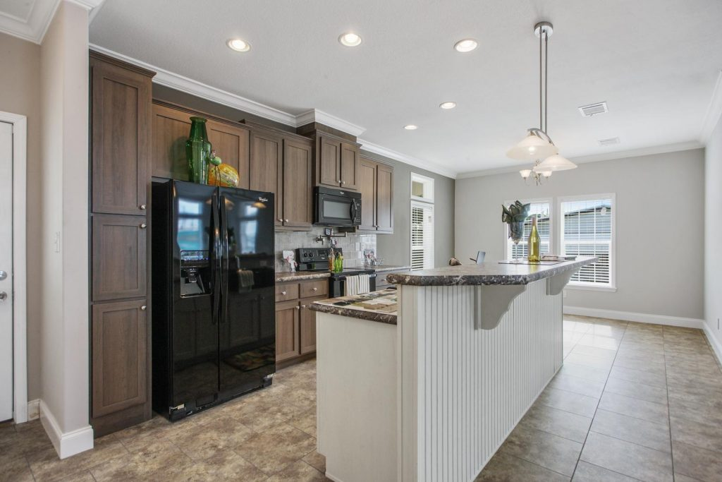 Modern kitchen with brand new fridge, microwave, and oven. Recessed lighting with dark wood cabinets floor to ceiling. Large kitchen island with breakfast nook and tile flooring throughout.