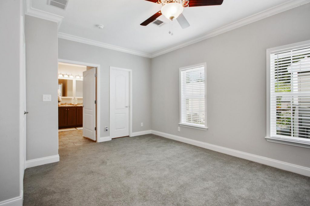 Bedroom with attached bathroom. Light gray walls with crown molding top and bottom and plush gray carpet. Two windows with blinds. Ceiling fan included.