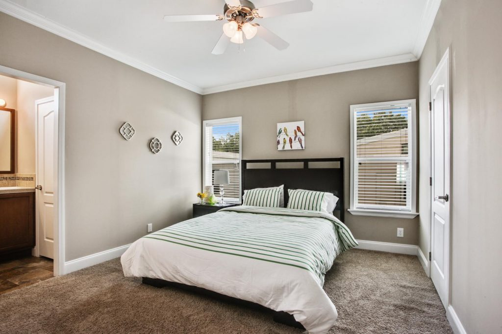 Bedroom with attached bathroom. Light gray walls with crown molding on top and bottom. Two windows. Queen sized bed with dark wood headboard and end table. Light brown carpeting.