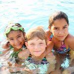 Three smiling girls swimming in pool.
