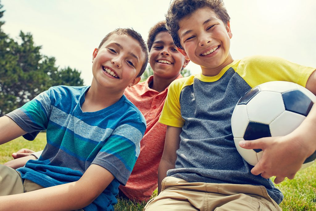 3 young boys smiling and sitting on the grass with soccer ball.