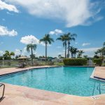 Palm Breezes Club, an active 55 plus manufactured home community, has a sparkling outdoor pool with lounge chairs all around pool area.