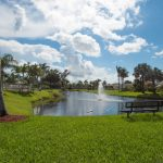 Beautiful, lush green grass surrounds the calm community lake. A fountain shoots off water in middle of lake. You can sit and gaze at the fountain from seating around the lake.