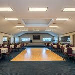 A clubhouse features a small dance floor and can fit many round tables with chairs to host banquets and events.