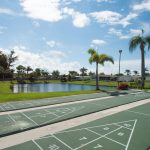 Palm Breezes Club has lots of amenities for its residents. Three shuffleboard courts are ready for play. Located next to lake. Bench seating at end of courts.