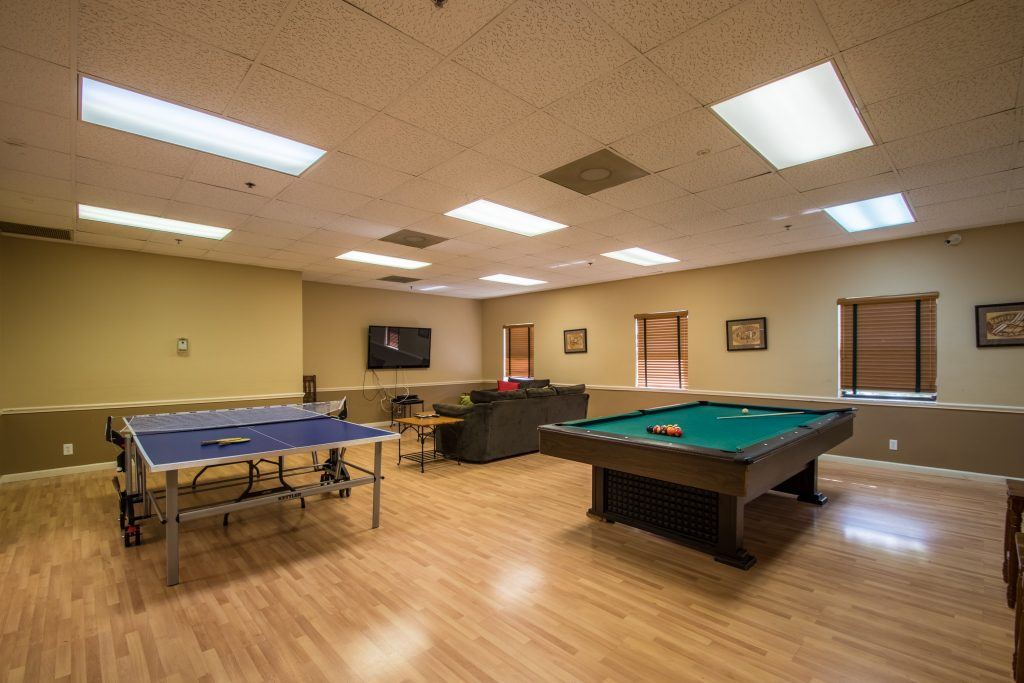 Palm Beach Plantation, an all age manufactured home community, offers a large game room with a pool table and ping pong. A loveseat and a flat screen tv are set up for movie time.
